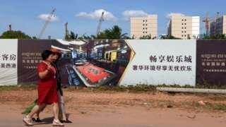Khách du lịch Trung Quốc đi ngang qua một công trình xây dựng một sòng bài do người Trung Quốc đầu tư ở thành phố Sihanoukville, tỉnh Phreah Sihanouk.