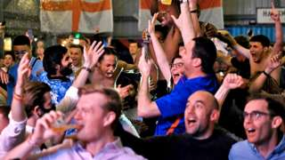 Fans celebrate as they watch a live broadcast of the semi-final match between England and Denmark at Hackney Bridge