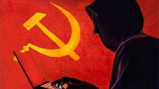 "The old Communist Russian hammer and sickle is seen in the background of a silhouetted ""hacker"" caricature wearing a hoodie"