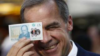 Mark Carney poses with a new polymer five pound note in London