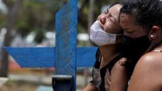 Kelvia Andrea Goncalves, 16, é amparada pela tia, Vanderleia dos Reis Brasao, 37, durante enterro da mãe, Andrea dos Reis Brasao, 39, no cemitério Parque Taruma em Manaus, Brasil