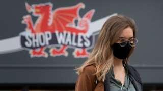 Woman wearing mask walks past 'Shop Wales' sign
