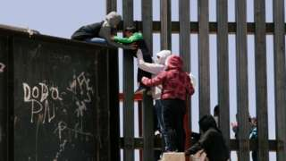 A small boy is passed over a border wall in the US.