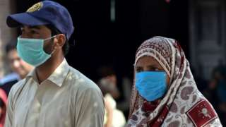 Residents wear protective facemasks as a prevention measure against the Covid-19 coronavirus on a street in Multan in Pakistan