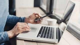 Usuário com laptop e smartphone