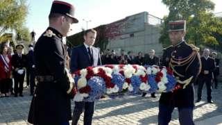 French President Emmanuel Macron lays a wreath of flowers near the Pont de Bezons