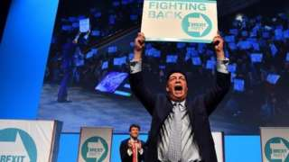 Nigel Farage holding poster aloft at Brexit Party rally