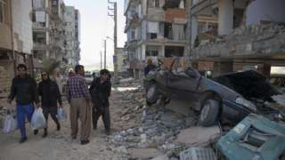 people walking past a car squashed under rubble in a street where parts of buildings have collapsed