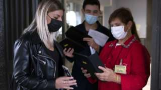"""School staff check for """"green pass"""" certificates at a school in Turin, Italy, 13 September 2021"""