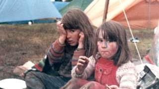 Two children sitting on the ground with tents behind them