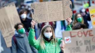 Climate change protesters wearing masks march in Bonn, Germany, March 2019