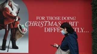 Woman wearing mask walking past Christmas poster