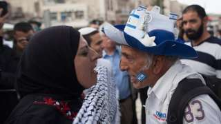 A pro-Palestinian woman and a pro-Israeli man shouting at each other