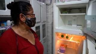Lindinalva olha para a geladeira vazia na casa dela