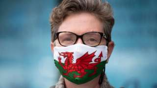 Woman wearing mask with Welsh flag on