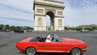 A convertable car in front of the Arc de Triomphe