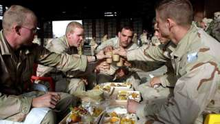 United States Army soldiers toast each other before eating Christmas dinner December 25, 2001 at Bagram Air Force Base