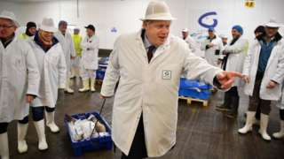 Boris Johnson drags a crate of fish