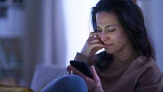 A woman looks upset while looking at her mobile phone