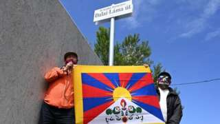 Activists hold the Tibetan flag underneath a street sign reading Dalai Lama Street in Budapest