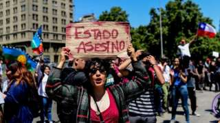 People demonstrate in front of the Presidential Palace, known as La Moneda, in Santiago, Chile on October 28, 2019