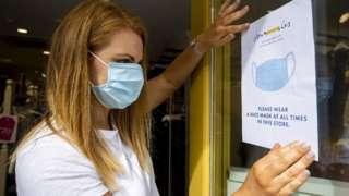 Shop owner holding up sign enforcing mask wearing in a shop