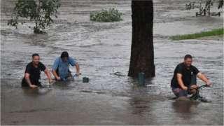 Three men push bikes through waist-deep water