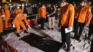 Indonesian search and rescue officers inspect a bag with wreckage believed to be of the missing Sriwijaya Air plane, at Tanjung Priok port in Jakarta, Indonesia, 10 January 2021