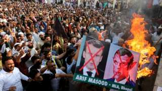 Indian Muslims hold placards as they protest against French President Emmanuel Macron