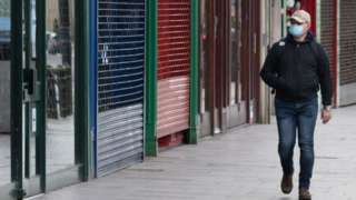 Man walking passed closed shops