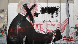 """Palestinian children walk past vandalised graffiti depicting US President Donald Trump and slogans saying US Vice-President Mike Pence is """"not welcome"""" in Bethlehem, West Bank. Photo: 7 December 2017"""