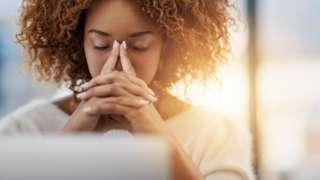 Une femme qui réflécit intensément devant son ordinateur