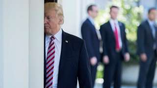 Donald Trump stands half hidden behind a post at the White House