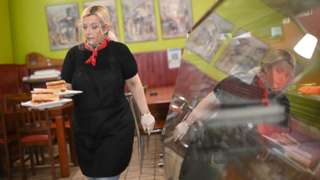 A worker carries a customer's breakfast order of bacon and sausage sandwiches table inside Barbarella's cafe in London. May 2021