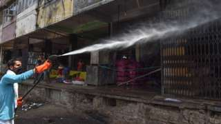 A sanitation worker spraying disinfectant over shops in Azadpur Mandi, on May 1, 2020 in New Delhi, India.