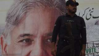 A Pakistani policeman stands guard beside an election poster featuring an image of Shahbaz Sharif, the younger brother of ousted Pakistani prime minister Nawaz Sharif and the head of Pakistan Muslim League -Nawaz (PML-N), Karachi 25 June 2018