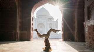 Mulher faz posição de ioga de cabeça pra baixo dentro de templo histórico na Índia