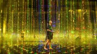People walk through a large colourful art installation