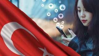 मोबाइल देखतीं एक महिला और तुर्की का झंडा
