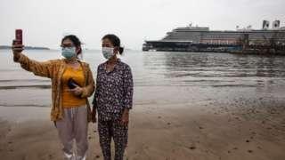 Mujeres tomándose foto con el crucero de fondo