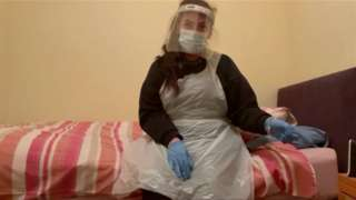 Care worker in PPE sits on bed