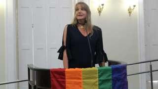 Marina Reidel fala em tribuna, na qual está pendurada bandeira do arco-íris
