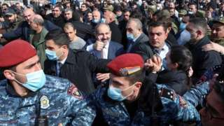 Armenian Prime Minister Nikol Pashinyan gives thumbs up (centre) surrounded by supporters and police in Yerevan. Photo: 25 February 2021