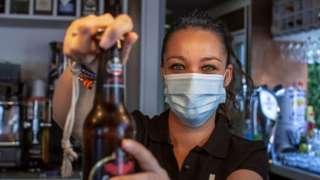 Una camarera sirve una cerveza