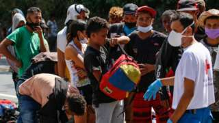 Venezuelan migrants wear a face masks as they queue to receive food and medicines from members of the Red Cross on a highway in Cucuta