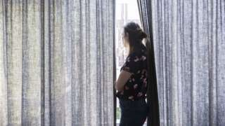 A woman looking out of her window between drawn curtains