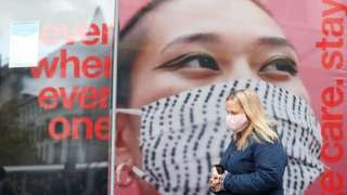 A person wearing a face mask walks down Market Street in Manchester