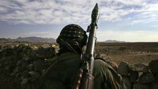 A soldier look out on Afghan terrain
