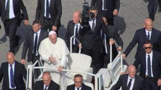Papa Francisco em carro aberto, cercado por seguranças, em 2019