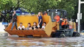 Rescue workers evacuate stranded residents with a bulldozer on a flooded street on 11 August after typhoon Lekima hit Taizhou, Zhejiang province.